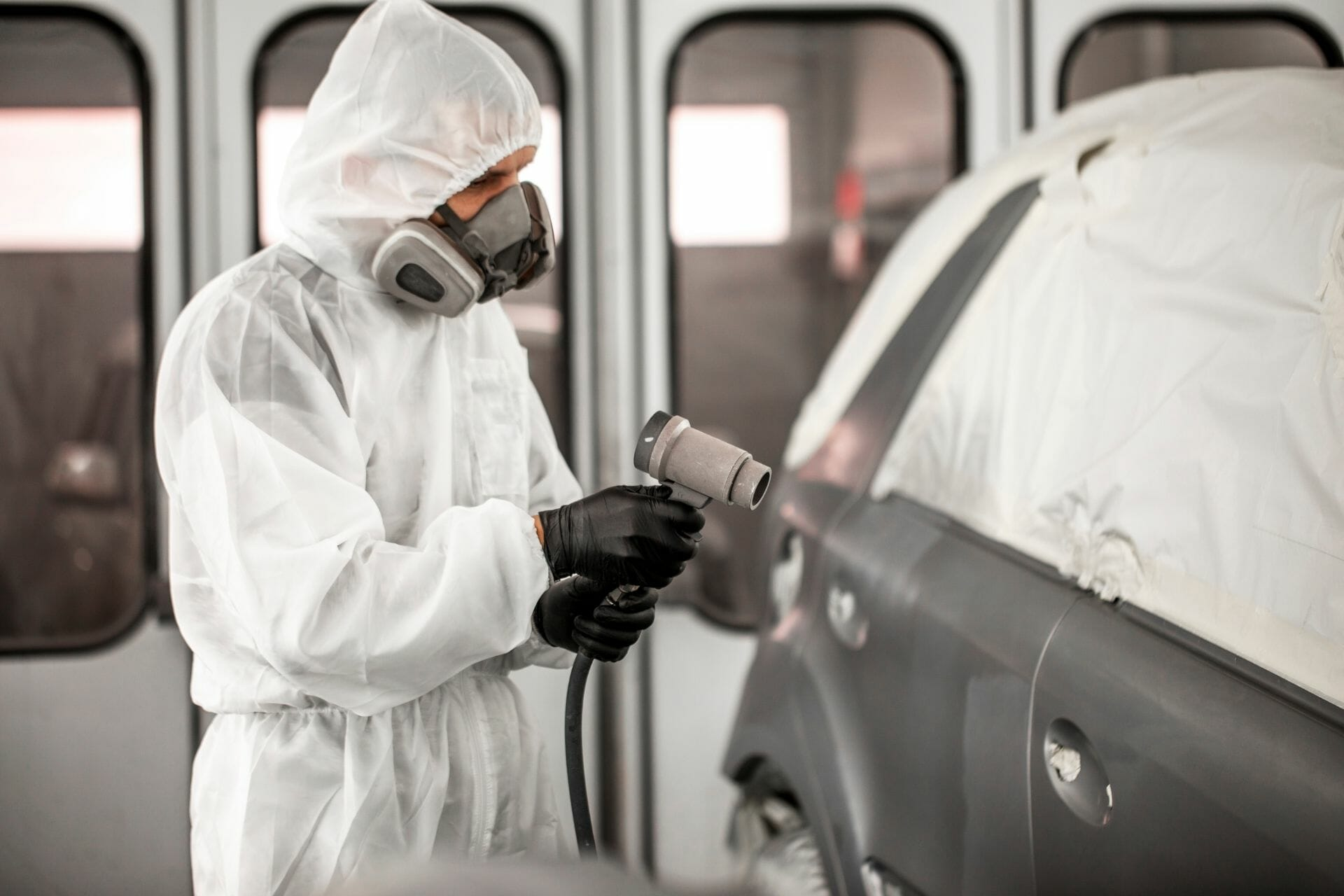 car technician spraying grey paint