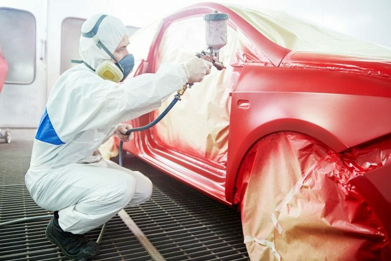 car technician wearing white suit spraying car in red