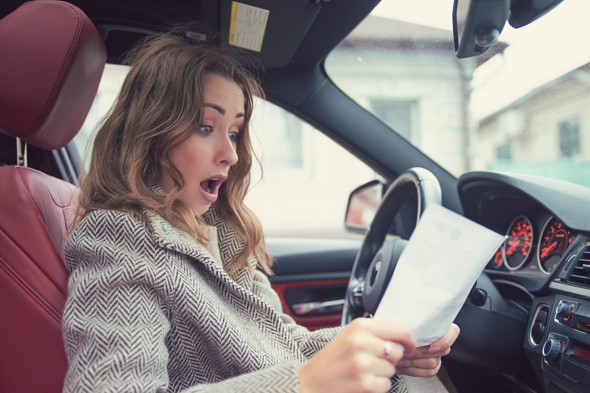 girl shocking holding a paper in car