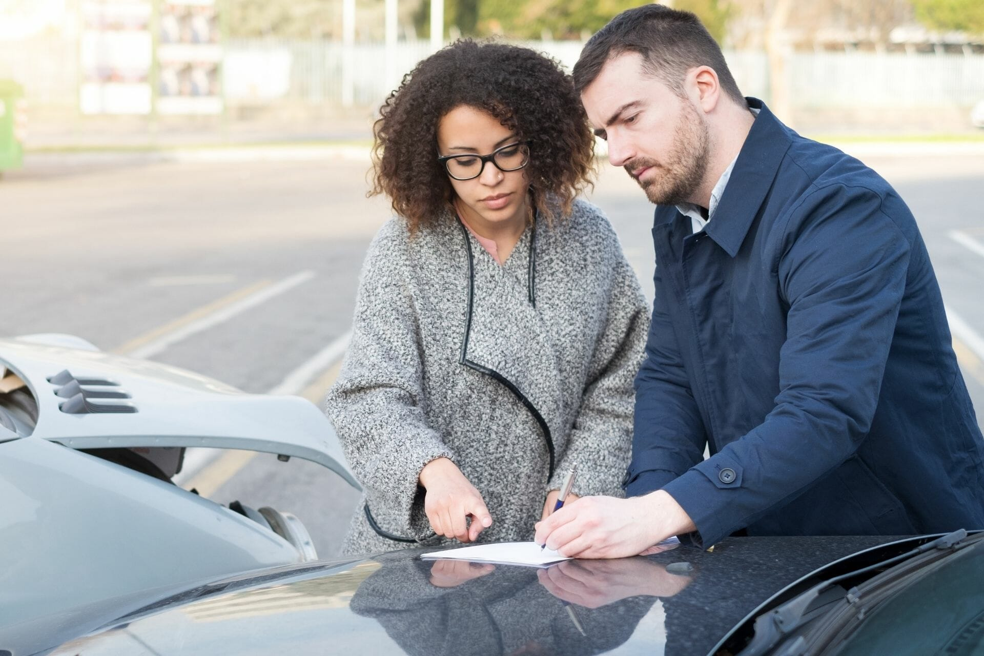 man and woman writing on paper outside on a car