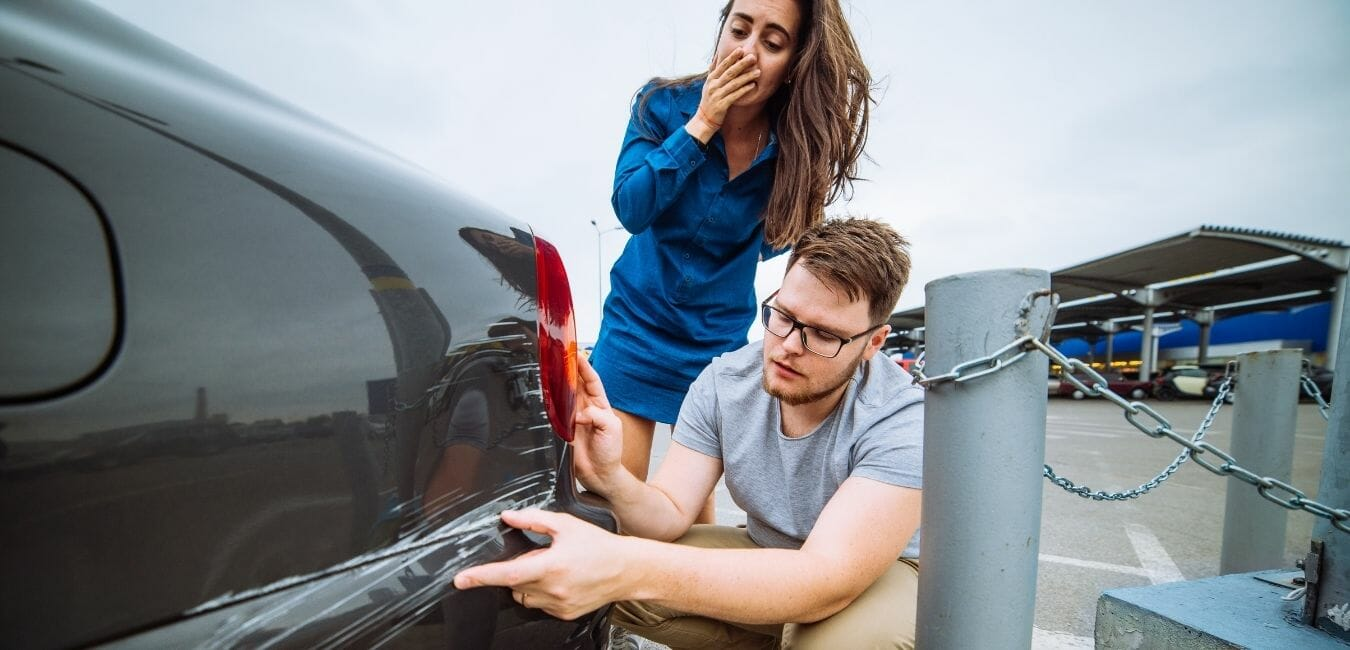man and woman with car dent after accident