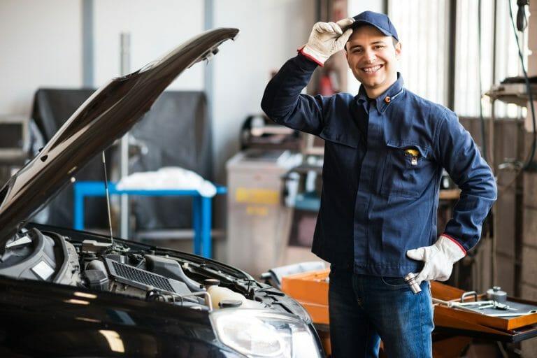 smiling technician in car workshop